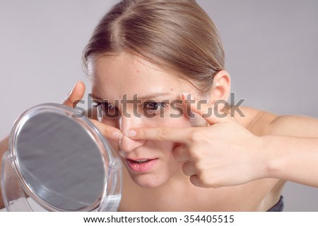 Young woman squeeze her acne in front of the mirror. Woman skin care concept
