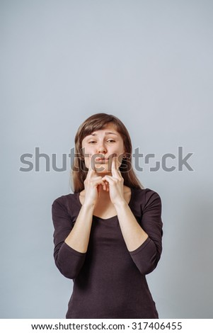 Young woman squeezing her cheeks with her hands - stock photo