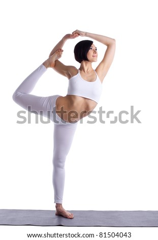 young woman stand in yoga pose on rubber mat - stock photo