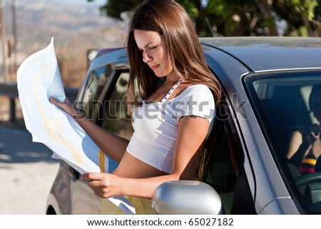 Young woman stand near the car and look on map - stock photo