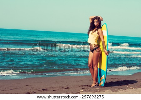 young woman stand on beach hold surfboard , sunny summer day, full body shot - stock photo