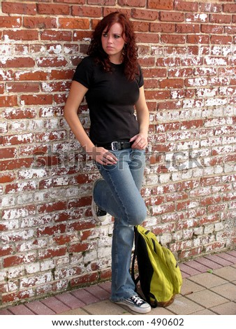 Young woman standing against wall with bookbag - stock photo