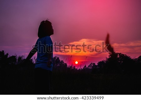 Young woman standing alone in a field during sunset. Silhouette of a young girl outdoor. - stock photo