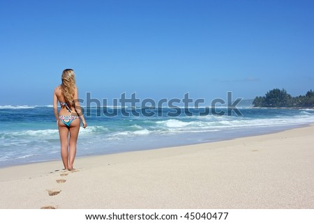 Young woman standing alone on the beach