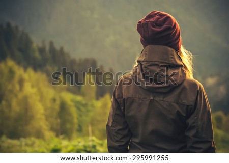 Young Woman standing alone outdoor with wild forest mountains on background Travel Lifestyle and survival concept rear view - stock photo