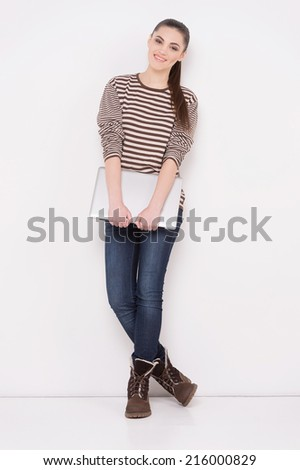 young woman standing and holding laptop. Happy young girl using her laptop, isolated on white.  - stock photo