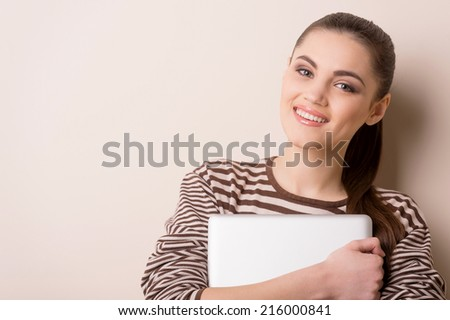 young woman standing and holding laptop. Happy young girl with her laptop, isolated on white.  - stock photo