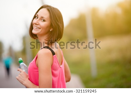 Young woman standing and resting after run, wellness and sport concept - stock photo