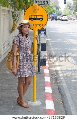 Young woman standing at a bus stop on street of city. Asian woman waiting for the bus. Woman in summer dress standing at the bus stop. Public transport stop in Thailand. Signs bus stops on the street.