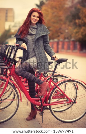 Young woman standing at city bike. - stock photo