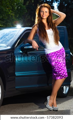 Young woman standing at her car. - stock photo