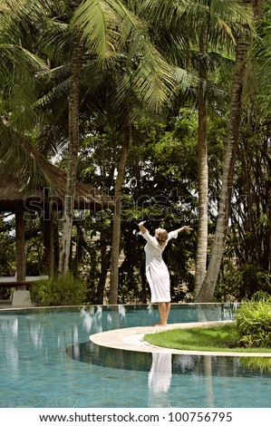 Young woman standing at the edge of a swimming pool surrounded by tall palm trees, with her arms outstretched in the air. - stock photo