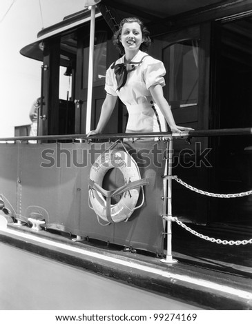 Young woman standing at the railing of a boat and smiling - stock photo