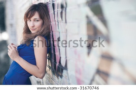 Young woman standing at the wall. Low contrast and shallow dof effect.