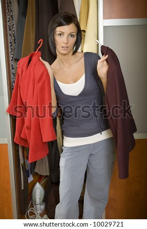 Young woman standing at wardrobe and chooses what can to dress. looking at camera. Front view. - stock photo