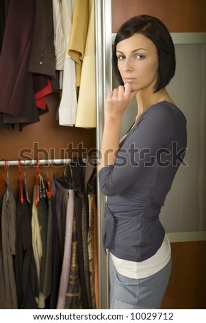 Young woman standing at wardrobe. She thinking what get dressed. Looking at camera. - stock photo