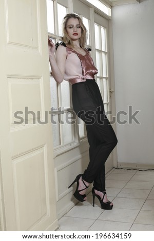 young woman standing before emitting doors, background light ,  beautiful girl in high hills standing before emitting doors, background light  - stock photo