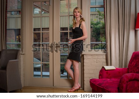 Young woman standing beside a door in a black dress
