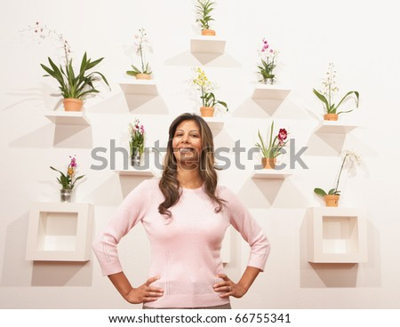 Young woman standing by a wall of flowers - stock photo