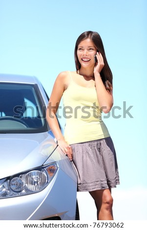 Young woman standing by car talking on mobile phone. Happy smiling mixed race Caucasian Asian woman on a beautiful bright sunny summer day.