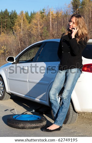 Young woman standing by her damaged car and calling for help - stock photo