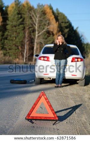 Young woman standing by her damaged car and calling for help. Focus is on the red triangle sign. Shallow depth of view. - stock photo