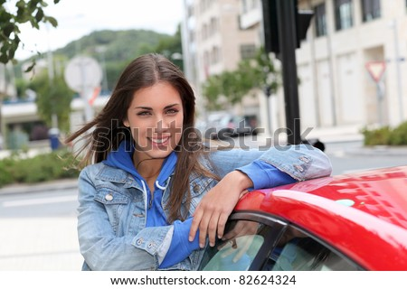 Young woman standing by red car - stock photo