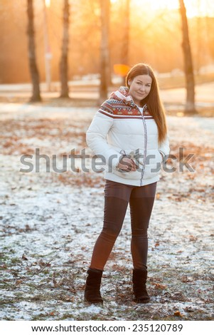 Young woman standing full-length in the winter park in sunset light - stock photo