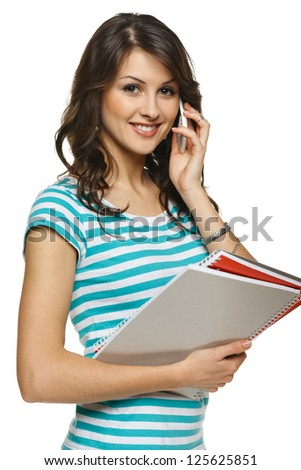 Young woman standing holding folders talking on mobile phone, over white background