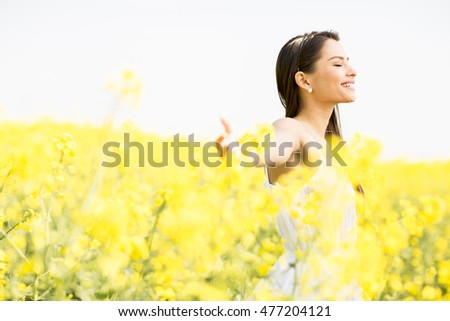Young woman standing in a field of yellow flowers on a sunny day