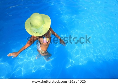 Young woman standing  in a swimming pool - stock photo