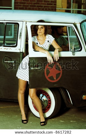 Young Woman standing in alley next to old van. - stock photo
