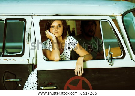 Young Woman standing in door of (old school) van. - stock photo