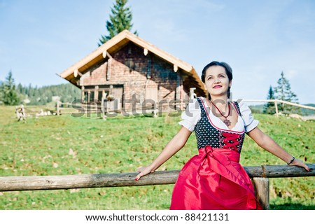 Young woman standing in front of a hut in the alps