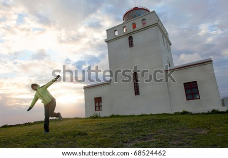young woman standing in front of Dyrhlaey lighthouse during sunset, Iceland - stock photo