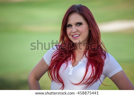 Young woman standing in front of green park trees with bright red hair headshot portrait
