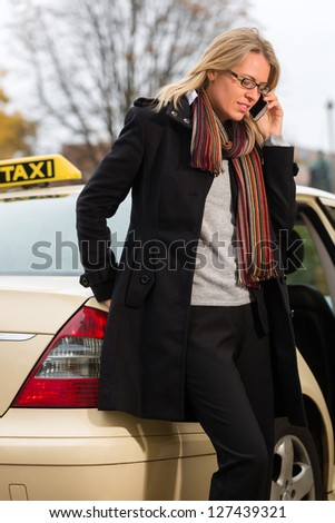 Young woman standing in front of taxi, she gets phone call - stock photo