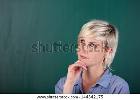 Young woman standing in front of the blackboard and thinking about something. - stock photo
