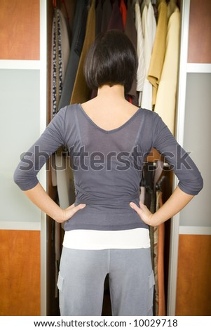 Young woman standing in front of wardrobe. She thinking what get dressed. She standing back to camera. - stock photo