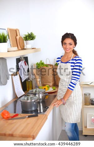 Young woman standing in her kitchen - stock photo