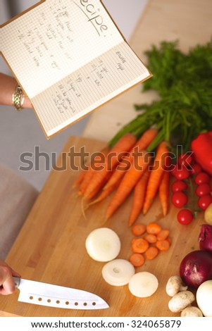 Young woman standing in her kitchen near desk with vegetables - stock photo