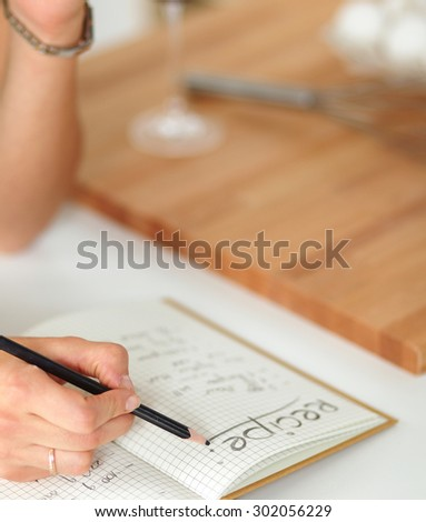 Young  woman standing in her kitchen writing on a notebook at home - stock photo