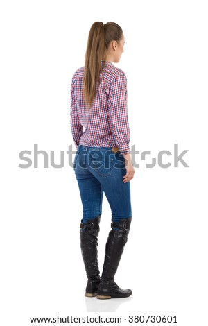 Young woman standing in jeans, black boots and lumberjack shirt. Rear side view. Full length studio shot isolated on white. - stock photo