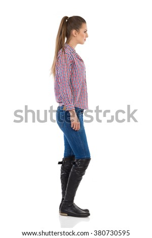 Young woman standing in jeans, black boots and lumberjack shirt. Side view. Full length studio shot isolated on white. - stock photo
