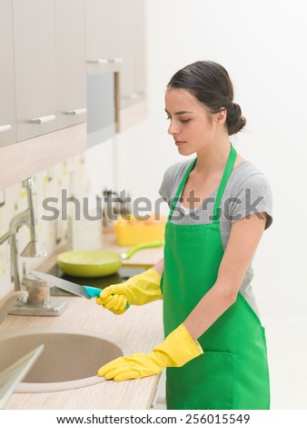 young woman standing in kitchen holding knife on top of sink, dishwashing