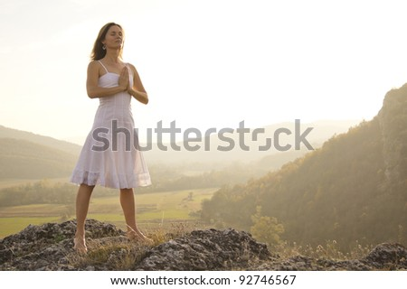 Young woman standing in meditation on the top of a hill - stock photo