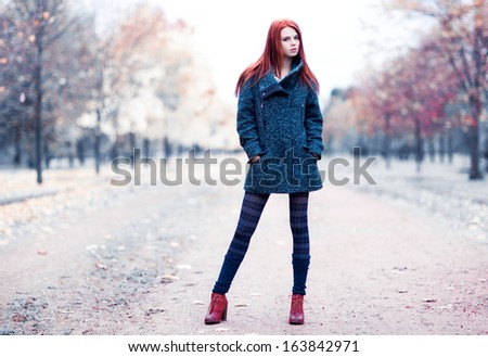 Young woman standing in park. Ir-style colors. - stock photo