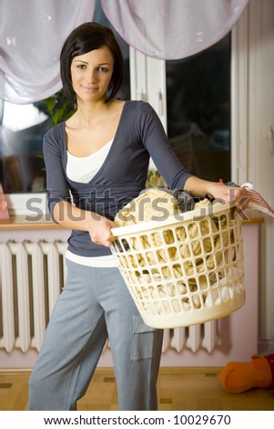 Young woman standing in room with full laundry basket. Looking at camera. Front view. - stock photo