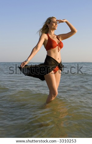 Young woman standing in the ocean, looking ahead.  Wearing red swimsuit. - stock photo