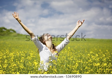 Young woman standing in yellow rapeseed field raising her arms expressing gratitude or freedom. - stock photo